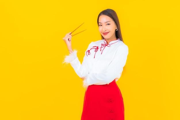 Retrato hermosa joven asiática con palillos listos para comer en amarillo