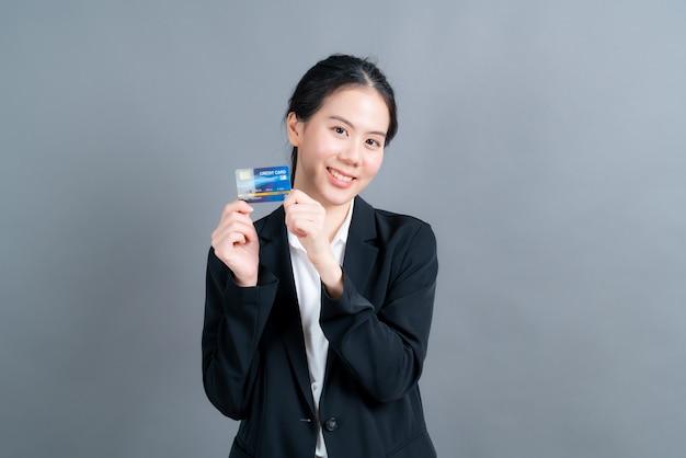 Retrato de una hermosa joven asiática en paños de oficial mostrando tarjeta de crédito con espacio de copia sobre fondo gris
