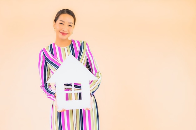 Retrato hermosa joven asiática con papel de signo de casa o casa en color