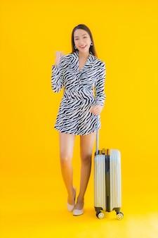 Retrato hermosa joven asiática con pasaporte de equipaje de viaje y tarjeta de embarque en amarillo