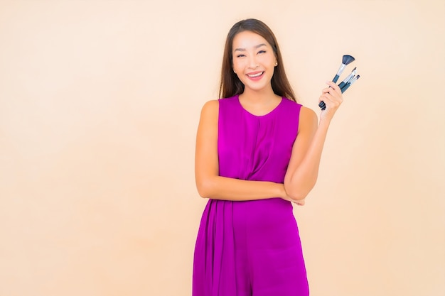 Retrato hermosa joven asiática con pincel de maquillaje sobre fondo de color aislado