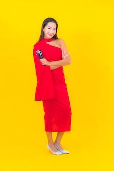 Retrato hermosa joven asiática con pincel de maquillaje