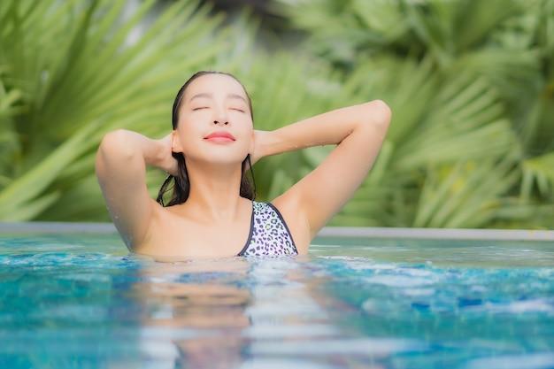 Retrato hermosa joven asiática relajante al aire libre en la piscina en viaje de vacaciones