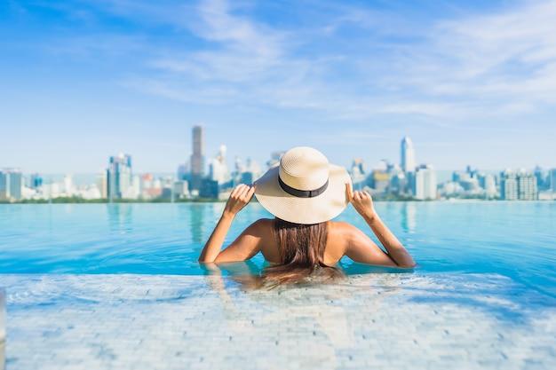 Retrato hermosa joven asiática relajante alrededor de la piscina al aire libre con vistas a la ciudad