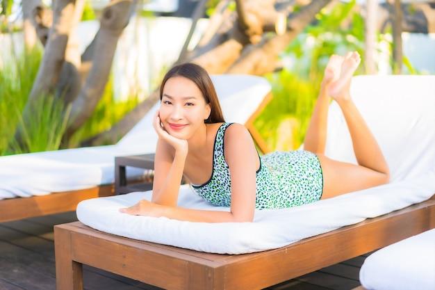 Retrato hermosa joven asiática relajante alrededor de la piscina en el hotel resort de vacaciones