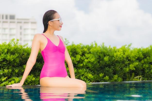 Retrato hermosa joven asiática relajarse disfrutar alrededor de la piscina al aire libre en vacaciones de vacaciones