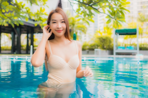 Retrato hermosa joven asiática relajarse feliz sonrisa ocio alrededor de la piscina al aire libre