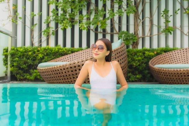 Retrato hermosa joven asiática relajarse ocio alrededor de la piscina al aire libre en el hotel resort para viajes de vacaciones