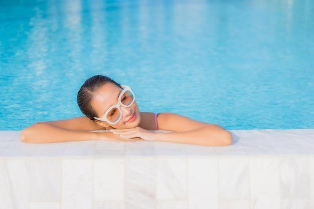Retrato hermosa joven asiática relajarse ocio alrededor de la piscina al aire libre con mar