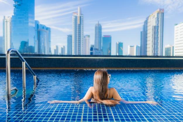 Retrato hermosa joven asiática relajarse ocio disfrutar alrededor de la piscina al aire libre