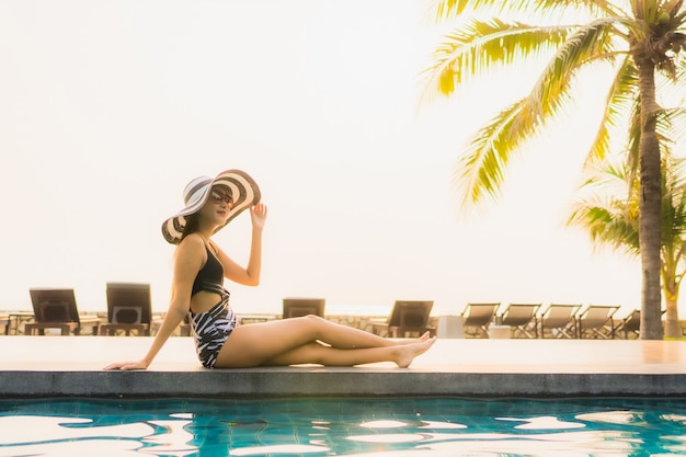 Retrato hermosa joven asiática relajarse en la piscina al aire libre en el hotel resort con palmera al atardecer o al amanecer