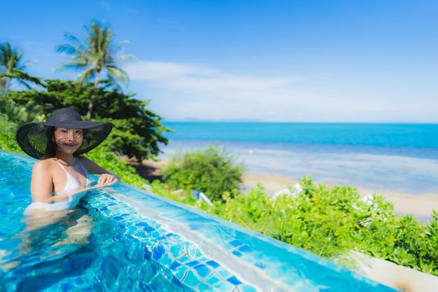 Retrato hermosa joven asiática relajarse en la piscina al aire libre de lujo en el hotel resort casi playa mar océano