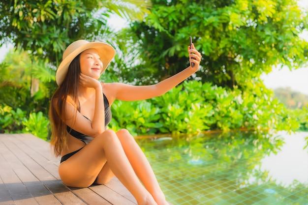Retrato hermosa joven asiática relajarse en la piscina en el hotel resort para vacaciones de ocio