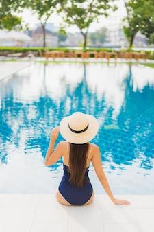 Retrato hermosa joven asiática relajarse sonrisa alrededor de la piscina al aire libre en el hotel resort en viajes de vacaciones