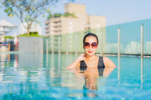 Retrato hermosa joven asiática relajarse sonrisa alrededor de la piscina al aire libre en el hotel resort