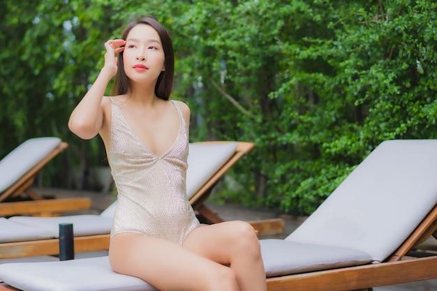 Retrato hermosa joven asiática relajarse sonrisa alrededor de la piscina al aire libre