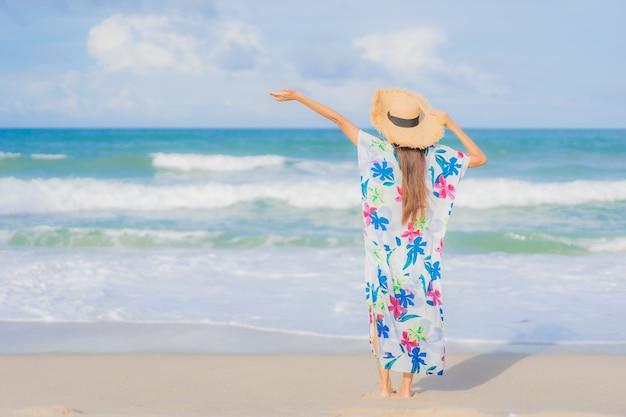 Retrato hermosa joven asiática relajarse sonrisa alrededor de la playa mar océano en vacaciones de vacaciones