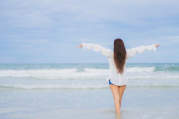 Retrato hermosa joven asiática relajarse sonrisa alrededor de la playa mar océano en viaje de vacaciones vacaciones
