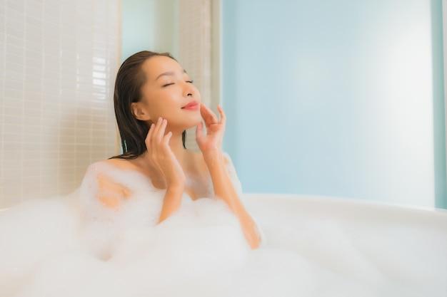 Retrato hermosa joven asiática relajarse sonrisa en la bañera en el interior del baño