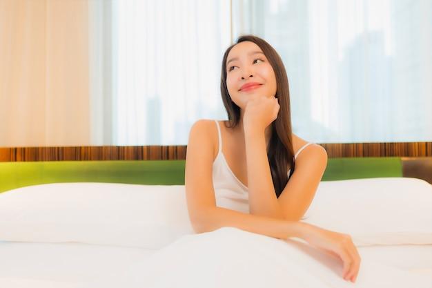 Retrato hermosa joven asiática relajarse sonrisa en la cama en el interior del dormitorio
