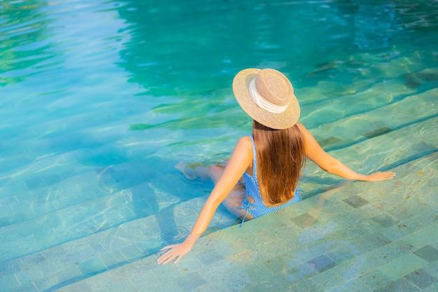 Retrato hermosa joven asiática relajarse sonrisa disfrutar de ocio alrededor de la piscina cerca de la playa con vistas al mar en vacaciones