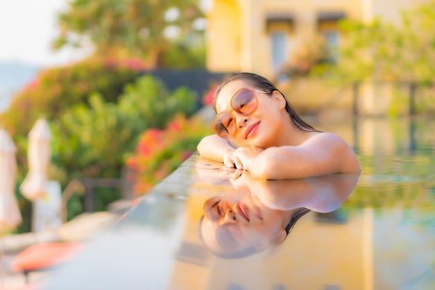 Retrato hermosa joven asiática relajarse sonrisa disfrutar de ocio alrededor de la piscina en el hotel resort de vacaciones