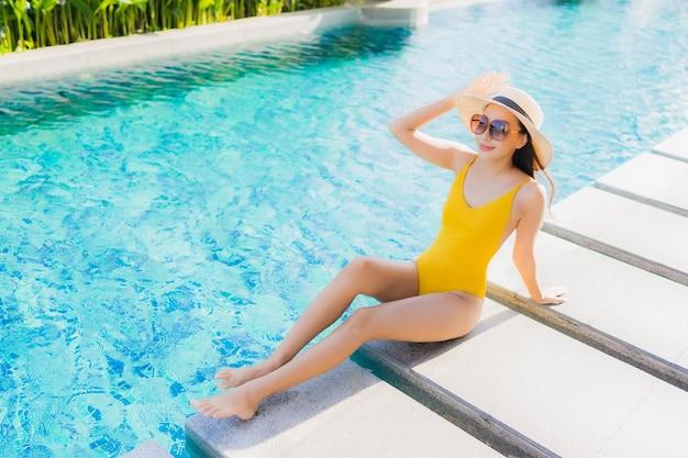 Retrato hermosa joven asiática relajarse sonrisa feliz alrededor de la piscina al aire libre en el hotel resort para vacaciones de ocio