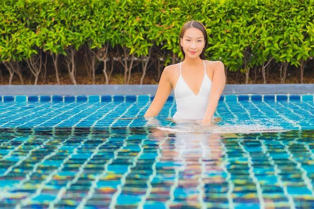 Retrato hermosa joven asiática relajarse sonrisa ocio alrededor de la piscina al aire libre cerca del mar
