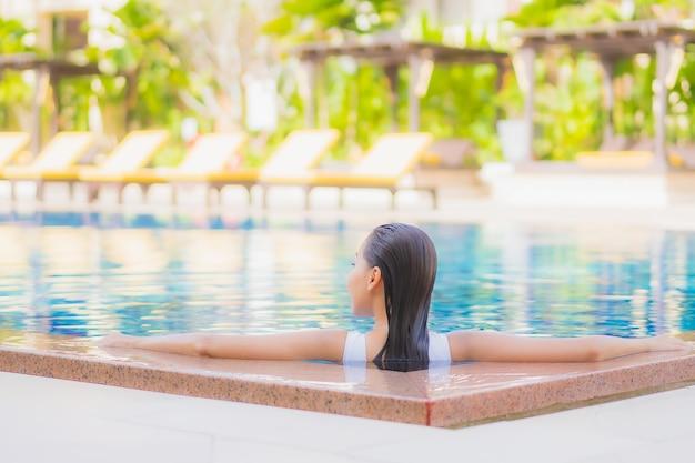 Retrato hermosa joven asiática relajarse sonrisa ocio alrededor de la piscina al aire libre en el hotel resort en viajes de vacaciones