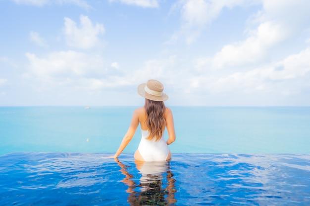 Retrato hermosa joven asiática relajarse sonrisa ocio alrededor de la piscina al aire libre con mar océano en vacaciones de viaje