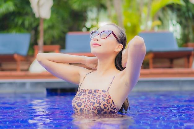 Retrato hermosa joven asiática relajarse sonrisa ocio alrededor de la piscina al aire libre en viajes de vacaciones vacaciones viajes