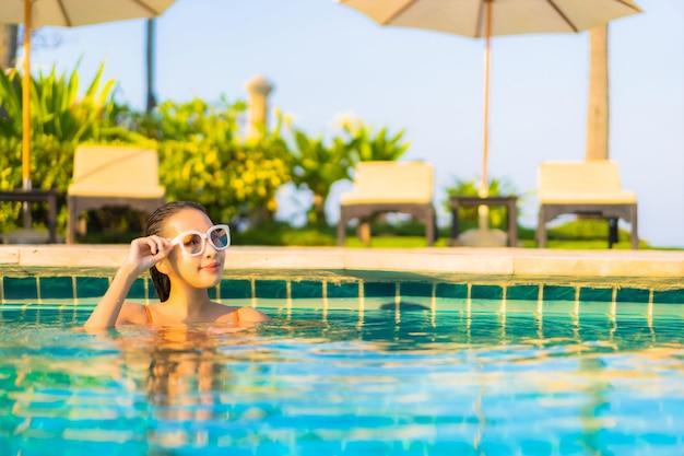 Retrato hermosa joven asiática relajarse sonrisa ocio alrededor de la piscina al aire libre con vista al mar