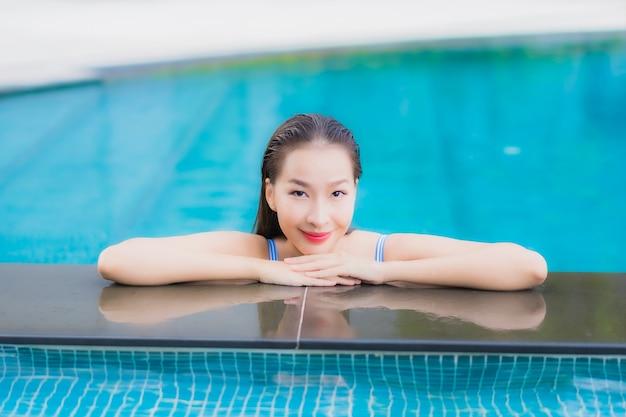 Retrato hermosa joven asiática relajarse sonrisa ocio alrededor de la piscina al aire libre