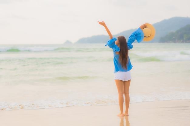Retrato hermosa joven asiática relajarse sonrisa de ocio alrededor de la playa mar océano al atardecer