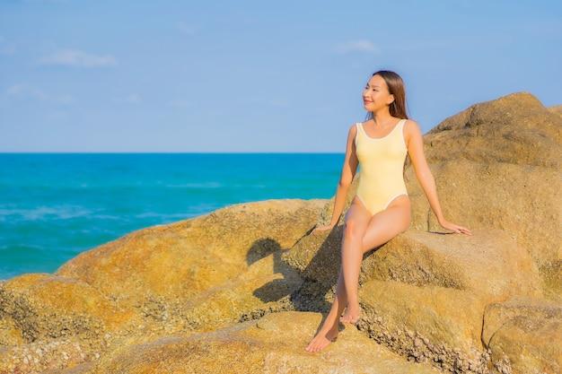 Retrato hermosa joven asiática relajarse sonrisa ocio alrededor de la playa mar océano en viaje viaje de vacaciones