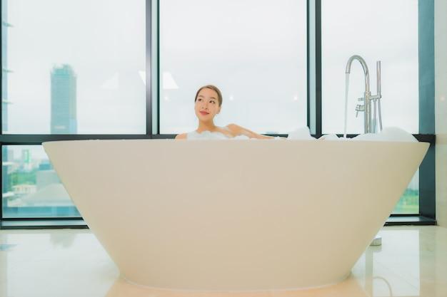 Retrato hermosa joven asiática relajarse sonrisa ocio en la bañera en el interior del baño