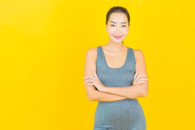 Retrato hermosa joven asiática con ropa deportiva lista para hacer ejercicio en la pared amarilla