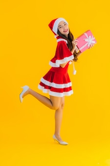 Retrato hermosa joven asiática ropa de navidad y sombrero sonrisa feliz con caja de regalo roja