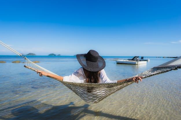 Retrato hermosa joven asiática sentada en una hamaca alrededor del mar playa océano para relajarse