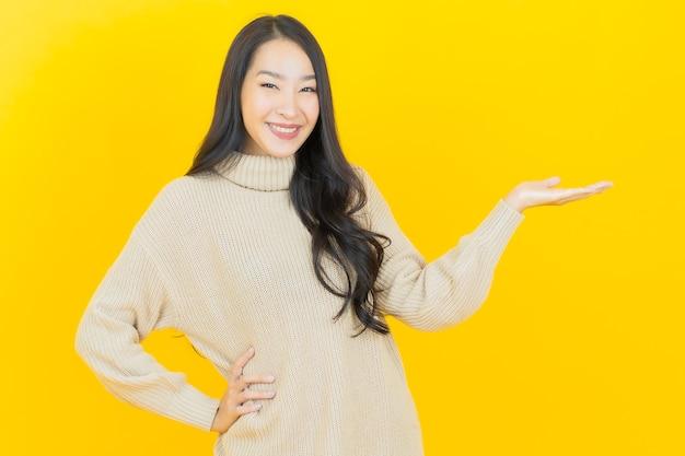 Retrato hermosa joven asiática sonríe con acción en la pared amarilla