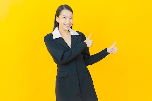 Retrato hermosa joven asiática sonríe con acción en la pared de color