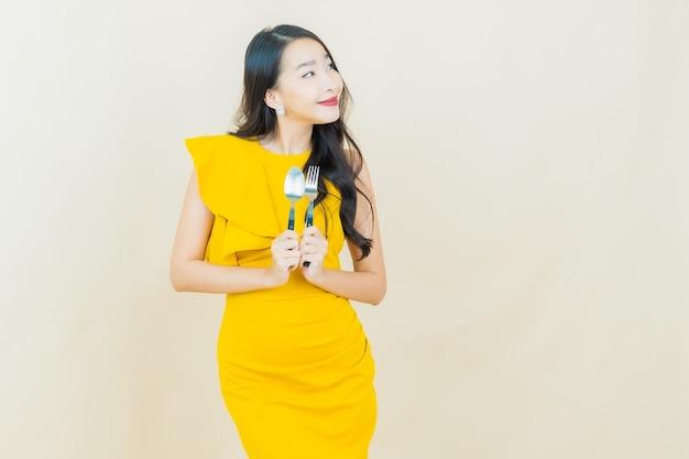 Retrato hermosa joven asiática sonríe con cuchara y tenedor en la pared beige