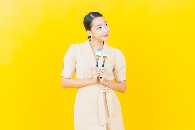 Retrato hermosa joven asiática sonríe con cuchara y tenedor en la pared de color