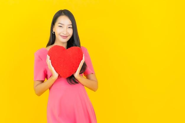 Retrato hermosa joven asiática sonríe con forma de almohada de corazón en la pared amarilla