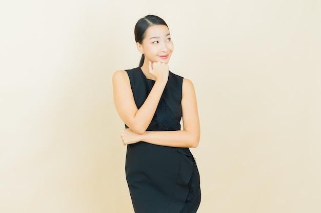Retrato hermosa joven asiática sonríe en la pared de color