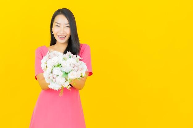 Retrato hermosa joven asiática sonríe con ramo de flores en la pared amarilla