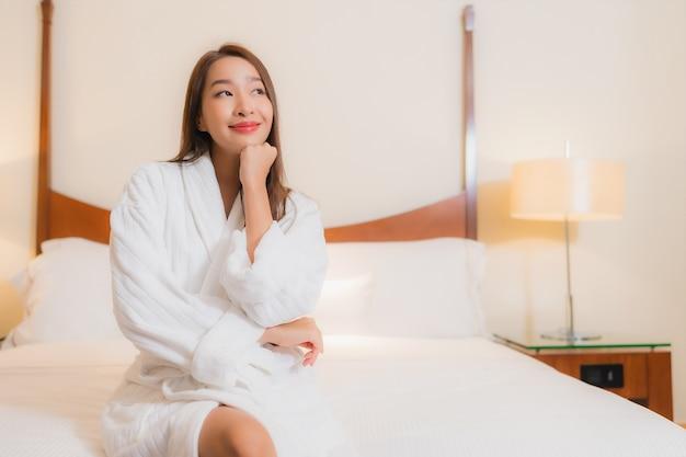 Retrato hermosa joven asiática sonríe relajante en la cama en el interior del dormitorio