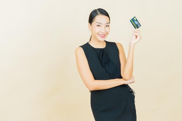 Retrato hermosa joven asiática sonríe con tarjeta de crédito en la pared de color