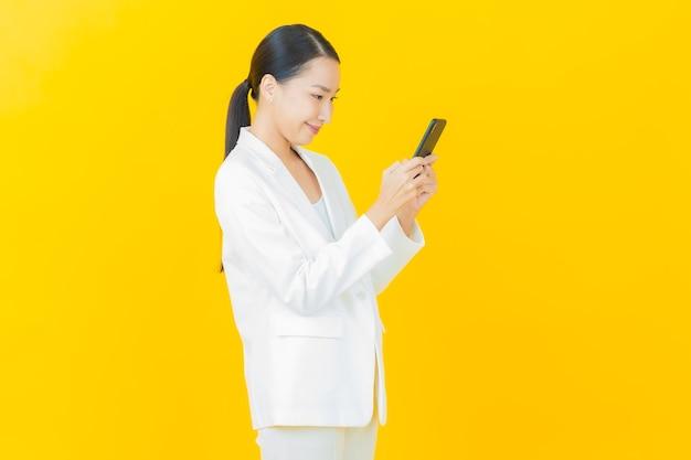 Retrato hermosa joven asiática sonríe con teléfono móvil inteligente en la pared de color