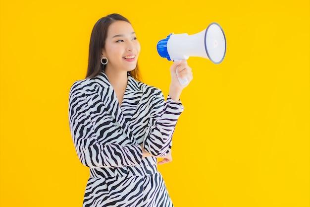 Retrato hermosa joven asiática sonrisa feliz con megáfono en amarillo